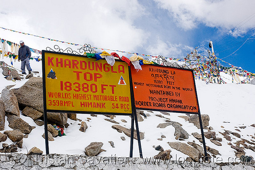 signs with incorrect (inflated) elevation - khardungla pass - ladakh (india), border roads organisation, bro road signs, buddhism, india, khardung la pass, ladakh, mountain pass, mountains, prayer flags, snow, tibetan