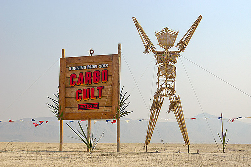 effigy near cargo cult entrance sign - burning man 2013, burning man, cargo cult, entrance, playa, sculpture, sign, the man