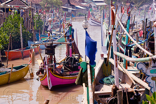 small fishing boats in fishing village - tamansarari, near probolingo (java), fisherman, fishing boats, fishing village, flags, indonesia, man, mooring, ropes, sailing, small boats, standing, steering, tamansari