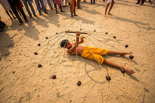 spinning balls with ropes (india), boy, game, hindu pilgrimage, hinduism, india, indian spinning balls, lying down, maha kumbh mela, metal balls, performer, ropes