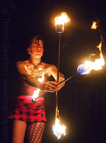 spinning crossed fire staffs - leah, fire dancer, fire dancing, fire performer, fire spinning, fire staffs, fire staves, flames, leah, night, tattooed, tattoos, woman