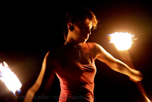 spinning fire staffs - fire dancer (san francisco) - leah, backlight, double staff, fire dancer, fire dancing, fire performer, fire spinning, fire staffs, fire staves, flame, leah, night, shadows, spinning fire, tattooed, tattoos, woman