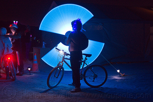 spinning light sabers, bicycle, bike, blue light, burning man, glowing, light sabers, light staff, night, silhouette