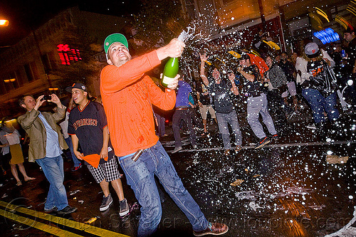 spraying champagne - SF giants fans celebrating, 2012 world series, alcohol, baseball fans, celebrating, champagne, crowd, editorial, go giants, man, night, partying, sf giants, sparkling wine, sports fans, spraying, street party