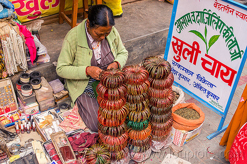 stacks of bracelets in street market (india), almora, bracelets, bundles, loose tea, selling, sign, sitting, stacks, stall, street market, street vendor, tea leaves, woman