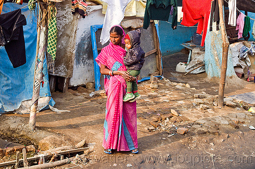 standing woman holding kid (india), baby, cloth lines, holding child, india, kid, pink saree, shanty house, shanty town, standing, toddler, village, woman