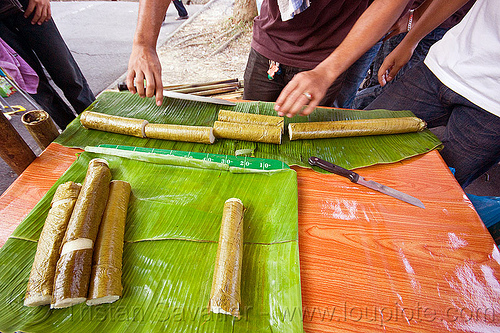 sticky rice in banana leaves cooked in bamboo, bamboo, banana leaves, borneo, cooked, cutting, food market, knife, malaysia, miri, ramadan market, sticky rice, street food, street market, street seller