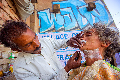 street barber shaving on the ghats - varanasi (india), graffiti, men, self-portrait, selfie, shaving, straight razor, street barber, tristan savatier, two, varanasi, wall
