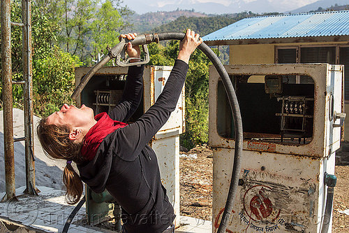 thirsty woman drinks at the petrol pump (nepal), anne-laure, bending backward, broken, drinking, gas pump, gas station, hose, nozzle, petrol pump, petrol station, woman