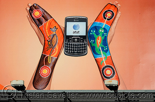 this AT&T billboard advertising strangely looks like the burning man logo, aboriginal art, advertising, at&t, australian, billboard, body art, body paint, body painting, boomerangs, burning man, cell phone, gecko, hands, logo, mobile phone, wireless