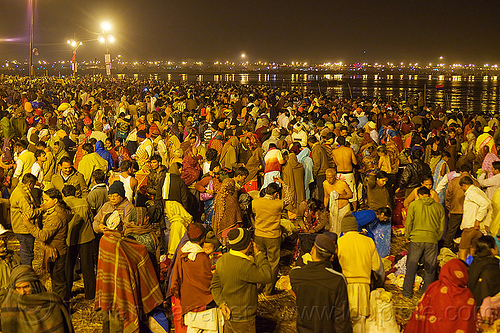 thousands of hindu pilgrims gathering for the holy bath in the ganges river at kumbh mela 2013 (india), crowd, hindu pilgrimage, hinduism, india, maha kumbh mela, men, night, paush purnima, pilgrims, street lights, triveni sangam, women