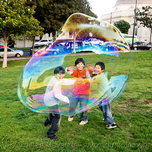 three kids behind a giant soap bubble, big bubble, children, giant bubble, iridescent, kids, lawn, park, playing, soap bubbles