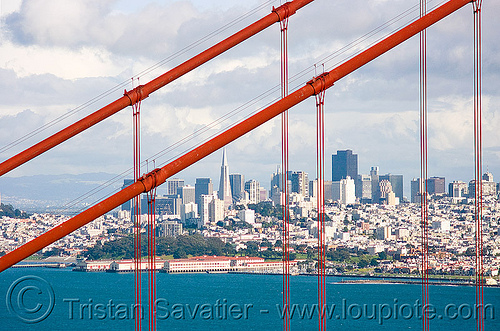 through the golden gate bridge - san francisco, buildings, cityscape, cloudy, coast, downtown, financial district, golden gate bridge, ocean, san francisco bay, san francisco skyline, sea, skyscrapers, suspension bridge, suspension cables, waterfront