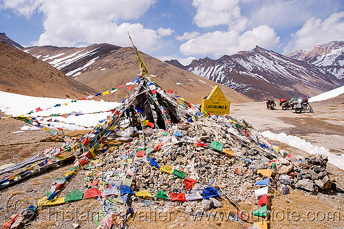 tibetan prayer flags on lachulung pass - manali to leh road (india), buddhism, lachulung pass, lachulungla, ladakh, motorbike touring, motorbikes, motorcycle touring, motorcycles, mountain pass, mountains, prayer flags, road, royal enfield bullet, snow patches, stone cairn, stones, tibetan