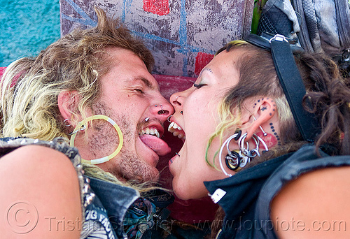 tongue biting, burning man, center camp, couple, ear piercing, sky nebeulah, sticking out tongue, sticking tongue out, woman