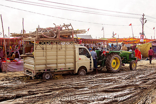 tractor pulling small truck stuck in mud (india), car, farm tractor, hindu, hinduism, kumbha mela, lorry, maha kumbh mela, mud ruts, muddy road, muddy street, stuck, towed, towing, truck