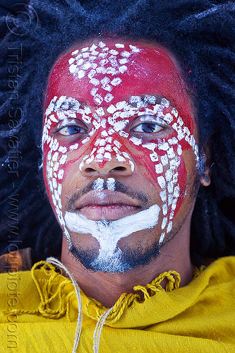 tribal face paint, african american man, african face paint, black man, dolores park, dreadlocks, dreads, face painting, facepaint, indigenous culture, jason, lying down, makeup, red, tribal face paint, white dots, yellow tunic