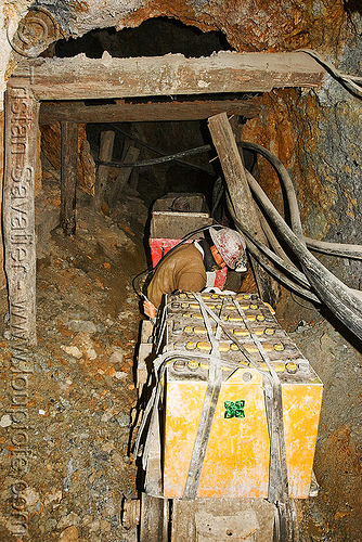 trolley carrying ore out of the mine, adit, batteries, beams, bolivia, cerro rico, electric, man, mina candelaria, mine tunnel, mine worker, miner, mining, pipes, potosí, safety helmet, trolley, underground mine, wood