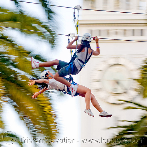 two girls riding the zip-line over san francisco, adventure, blue sky, cable line, cables, campanil, climbing helmet, clock tower, embarcadero tower, ferry building, hanging, mountaineering, moving fast, palm trees, sonia, speed, steel cable, trolley, tyrolienne, urban, women, zip line, zip wire