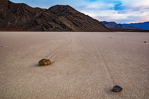 sailing stones on the racetrack - death valley, cracked mud, death valley, desert, dry lake, dry mud, mountains, racetrack playa, sailing stones, sliding rocks, tracks