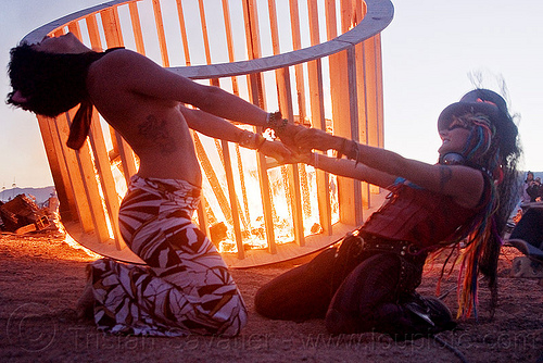 two women dancing - cylindrical wooden frame burning, burning man, cylinder, cylindrical, dancing, dusk, fire, flames, frame, heather, stretching, woman, wood, wooden