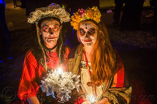 two women with sugar skull makeup - dia de los muertos (san francisco), candle, day of the dead, dia de los muertos, face painting, facepaint, flame, flower headdress, halloween, night, sugar skull makeup, white flowers, women