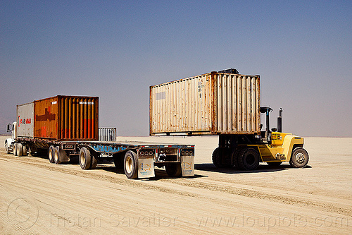 unloading containers from semi truck trailer - burning man 2012, articulated lorry, big rig, burning man, containers, flat bed, forklift, heavy equipment, hydraulic, machinery, semi trailer, semi truck, tractor-trailer, trucks, unloading