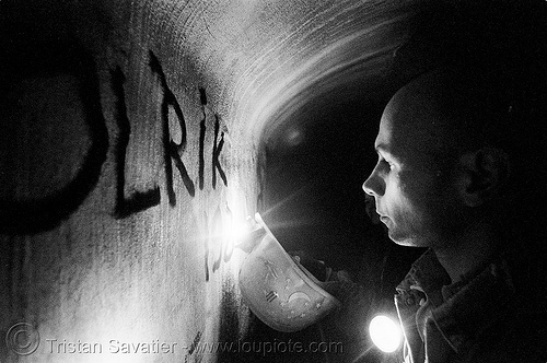 urban caver olrik writing on concrete wall of a utility tunnel with a carbide lamp (paris), acetylene, carbide lamp, catacombs of paris, cave, caving, gallery, graffiti, olrik, p3200tmz, safety helmet, shadow, spelunking, tag, tmax, trespassing, underground quarry, urban exploration, utility tunnel, wall