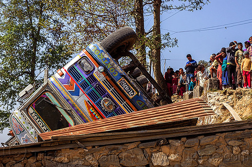 villagers looking at overturned truck (nepal), corrugated metal, crash, ditch, lorry, mountain road, overturned, people, rollover, tata motors, traffic accident, truck accident, up-side-down, wreck