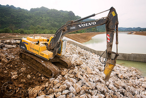volvo EC210 excavator - downstream canal - nam theun 2 hydroelectric project (laos), at work, attachment, construction, heavy equipment, hydraulic, hydraulic breaker, hydraulic hammer, hydro-electric, machinery, nam theun power company, ntpc, rocks, rubble, stones, volvo ec210b excavator, volvo ec210blc excavator, volvo excavator, working
