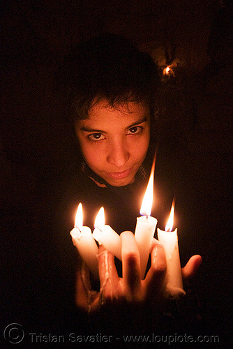 wax play - woman holding burning candles with dripping wax, candles, cataphile, cave, clandestines, fire, illegal, low key, new year's eve, paris, underground quarry, wax play, woman