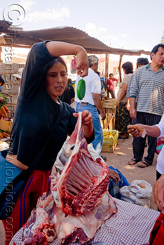 weighing a cut of llama meat (argentina), andean carnival, butcher, carnaval, llama, meat market, meat shop, noroeste argentino, quebrada de humahuaca, raw meat, ribs, spring weighing scale, street vendor, weighting scale, woman