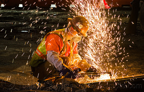 welder cutting a rail with an oxy-acetylene torch, dust mask, high-visibility jacket, high-visibility vest, light rail, man, muni, night, ntk, oxy-acetylene cutting torch, oxy-fuel cutting, railroad construction, railroad tracks, rails, railway tracks, reflective jacket, reflective vest, safety glasses, safety helmet, safety vest, san francisco municipal railway, sparks, track maintenance, track work, welder, worker, working