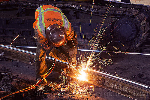 welder cutting a railroad track rail with an oxy-acetylene torch, demolition, high-visibility jacket, high-visibility vest, light rail, man, muni, night, ntk, oxy-acetylene cutting torch, oxy-fuel cutting, railroad construction, railroad tracks, railway tracks, reflective jacket, reflective vest, safety helmet, safety vest, san francisco municipal railway, sparks, track maintenance, track work, welder, welding, worker, working