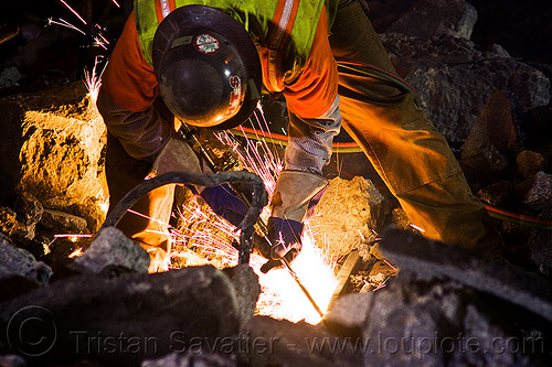 welder cutting a track rail with a oxy-acetylene torch, high-visibility jacket, high-visibility vest, light rail, man, muni, night, ntk, oxy-acetylene cutting torch, oxy-fuel cutting, railroad construction, railroad tracks, rails, railway tracks, reflective jacket, reflective vest, safety glasses, safety gloves, safety helmet, safety vest, san francisco municipal railway, sparks, track maintenance, track work, welder, worker, working