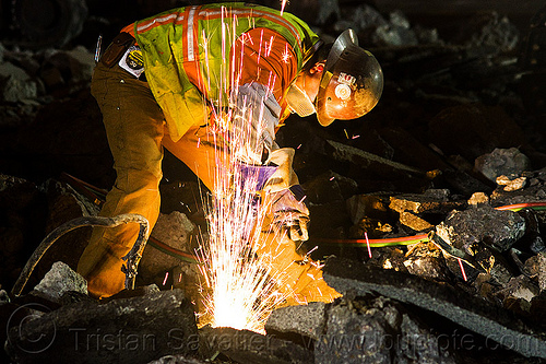 welder cutting a track rail with a oxy-acetylene torch, dust mask, high-visibility jacket, high-visibility vest, light rail, man, muni, night, ntk, oxy-acetylene cutting torch, oxy-fuel cutting, railroad construction, railroad tracks, railway tracks, reflective jacket, reflective vest, safety glasses, safety gloves, safety helmet, safety vest, san francisco municipal railway, sparks, track maintenance, track work, welder, worker, working