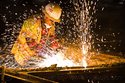 welder cutting a track rail with a oxy-acetylene torch, high-visibility jacket, high-visibility vest, light rail, man, muni, night, ntk, oxy-acetylene cutting torch, oxy-fuel cutting, railroad construction, railroad tracks, rails, railway tracks, reflective jacket, reflective vest, safety glasses, safety helmet, safety vest, san francisco municipal railway, sparks, track maintenance, track work, welder, worker, working