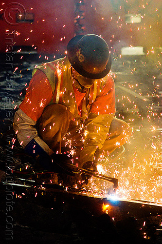 welder uses oxy-acetylene cutting torch to cut track rails, dust mask, fire, flames, high-visibility jacket, high-visibility vest, light rail, man, muni, night, ntk, oxy-acetylene cutting torch, oxy-fuel cutting, railroad construction, railroad tracks, rails, railway tracks, reflective jacket, reflective vest, safety glasses, safety helmet, safety vest, san francisco municipal railway, sparks, track maintenance, track work, welder, worker, working