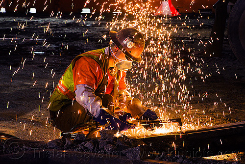 welder using an oxy-acetylene cutting torch, dust mask, high-visibility jacket, high-visibility vest, light rail, man, muni, night, ntk, oxy-acetylene cutting torch, oxy-fuel cutting, railroad construction, railroad tracks, rails, railway tracks, reflective jacket, reflective vest, safety glasses, safety helmet, safety vest, san francisco municipal railway, sparks, track maintenance, track work, welder, worker, working