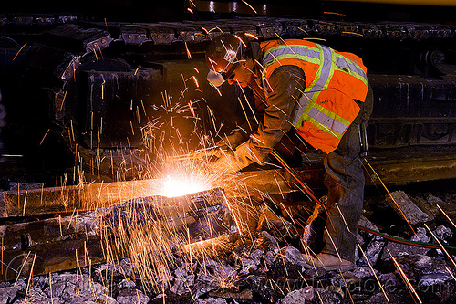 welder using cutting torch to cut a rail, demolition, high-visibility jacket, high-visibility vest, light rail, man, muni, night, ntk, oxy-acetylene cutting torch, oxy-fuel cutting, people, railroad construction, railroad tracks, rails, railway tracks, reflective jacket, reflective vest, safety helmet, safety vest, san francisco municipal railway, sparks, track maintenance, track work, welder, welding, worker, working