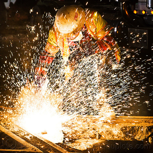 welder using oxy-acetylene cutting torch, dust mask, high-visibility jacket, high-visibility vest, light rail, man, muni, night, ntk, oxy-acetylene cutting torch, oxy-fuel cutting, railroad construction, railroad tracks, rails, railway tracks, reflective jacket, reflective vest, safety glasses, safety helmet, safety vest, san francisco municipal railway, sparks, track maintenance, track work, welder, worker, working