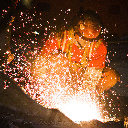 welder using oxy-acetylene cutting torch, high-visibility jacket, high-visibility vest, light rail, man, muni, night, ntk, oxy-acetylene cutting torch, oxy-fuel cutting, railroad construction, railroad tracks, rails, railway tracks, reflective jacket, reflective vest, safety glasses, safety helmet, safety vest, san francisco municipal railway, sparks, track maintenance, track work, welder, worker, working