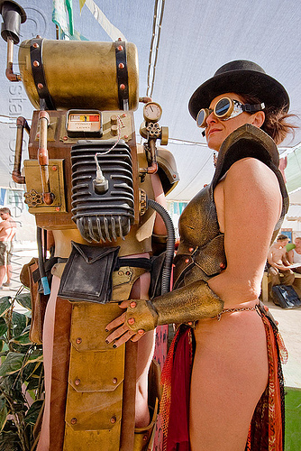 woman and golden robot, burning man, center camp, couple, cuffs, gauge, goggles, golden, hat, pipes, robot costume, spark plug, tank, woman