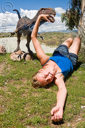 woman attacked by velociraptor, ania, bite, biting, dinosaur park, grass, hand, head, lying down, parque cretacico, parque cretácico, sucre, teeth, turf, velociraptor, woman