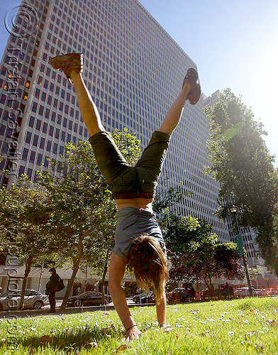 woman cartwheeling in park (san francisco), cartwheeling, catrwheel, city park, gymnastics, hirise building, jessika, lawn, trees, upside-down, woman