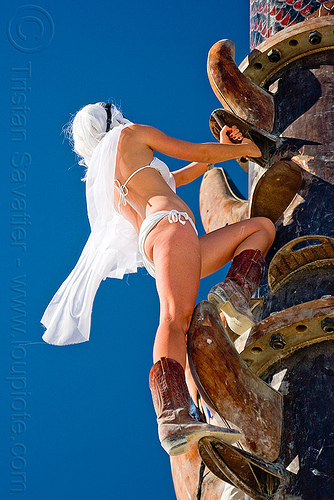 woman climbing the tower, boots, burning man, climbing, the minaret, white wig, woman