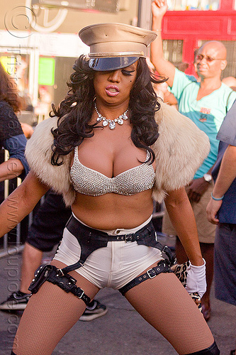 woman dancing - folsom street fair (san francisco), bra, fashion, fur, leather belt, leather straps, m2f, military cap, military hat, necklace, shorts, transgender, transsexual, transwoman