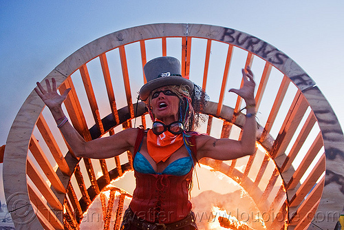 woman dancing near fire, burning man, cylinder, cylindrical, dusk, face painting, facepaint, fire, flames, frame, goggles, hat, makeup, woman, wood, wooden