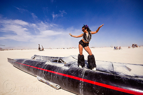 woman dancing on rocket car - burning man 2012, art car, black, black leg warmers, furry leg warmers, long, people