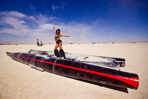 woman dancing on the rocket car - burning man 2012, art car, black leg warmers, burning man, dancing, furry leg warmers, long, necklaces, rocket car, woman